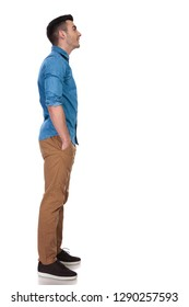 side view of relaxed casual man looking up at something while standing on white background