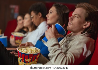 Side view of relaxed man lying on chair in cinema, drinking and eating tasty popcorn. Young male watching interesting movie and resting on weekends. Concept of film and entertainment.