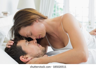 Side view of a relaxed young couple together in bed at home