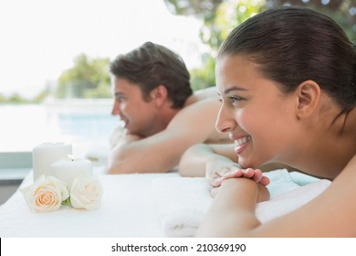 Side view of relaxed young couple lying on massage table at spa center