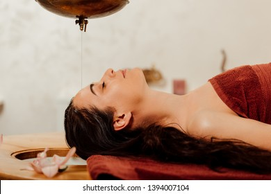 side view of relaxed young woman lying under shirodhara vessel during ayurvedic procedure