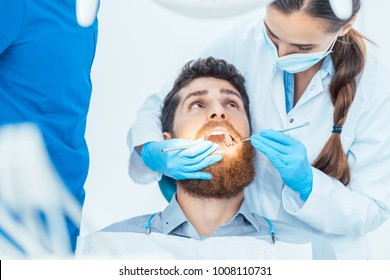 Side view of a reliable female dentist, using sterile instruments and blue surgical gloves while cleaning the teeth of a patient in the dental office of a modern clinic