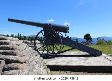 Side view of replica of Long Tom cannon with sandbags, set against scenic green background