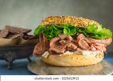 Side view of roast beef sandwich with lettuce on an everything bagel and a side of blue corn chips