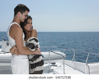 Side view of romantic young couple embracing on yacht with ocean in background