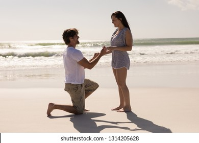 Side view of romantic young man proposing to a woman on his knee at beach in the sunshine