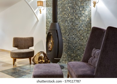 Side view of room with fireplace where burning fire and two violet armchair and table around. Basket with firewood near and elements of stone. Interior in violet, gray and white colors.