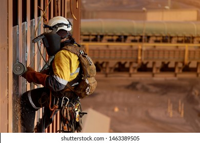 Side view of rope access technician welder services wearing white helmet head fall protection PPE, face shield abseiling working at height  using power grinder grinding wall preparation prior weld