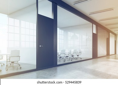 Side view of a row of meeting rooms in a long corridor. Glass walls, black doors. Concept of communication. 3d rendering. Toned image