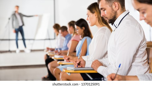 Side view of row of people listening lecturer and making notes at extension courses