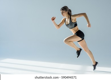 side view of running woman in sportive clothing on grey