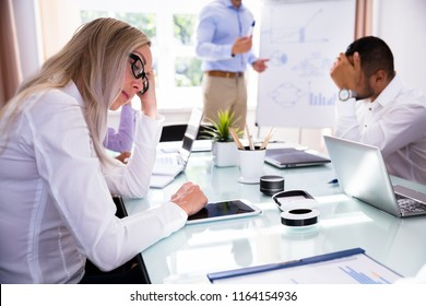 Side View Of A Sad Businesswoman Sitting In Office
