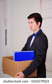 Side view of sad man holding a box after being fired form his job in a blurred background