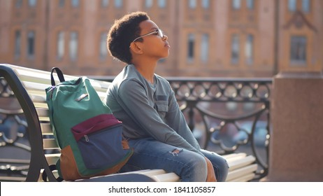 Side view of sad mixed-race schoolboy sitting alone on bench outdoors. Upset and worried african preteen boy with backpack sitting on street bench anxious about exam