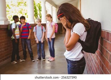 Side view of sad schoolgirl with friends in background at school corridor