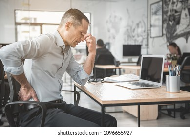 Side view sad tired worker rubbing eyes after long work with laptop. He situating at desk and feeling pain in back. Fatigue at job concept