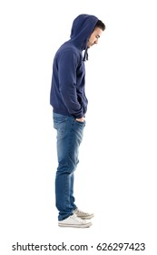 Side view of sad upset man in hooded shirt with hands in pockets looking down. Full body length portrait isolated over white studio background.