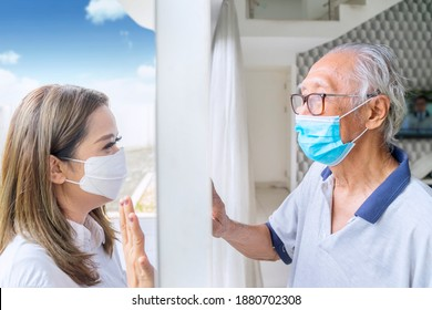 Side view of sad woman wearing a face mask while visiting her infected father and talking through window at home during Covid-19 outbreak - Shutterstock ID 1880702308