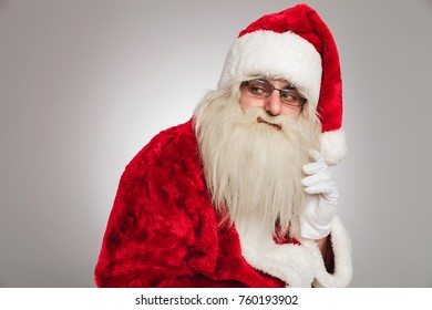 side view of santa claus thinking on grey backround