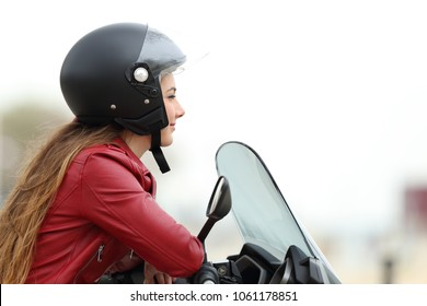 Side view of a satisfied biker looking away on a motorbike