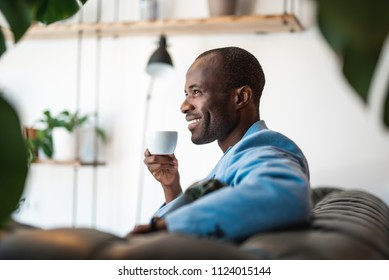 Side view satisfied man drinking mug of delicious beverage while relaxing on cozy sofa during break