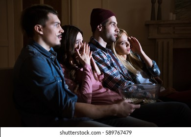 side view of scared friends watching movie with popcorn at home