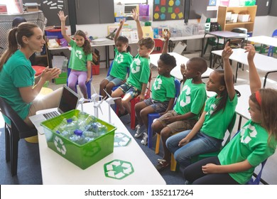 Side view of school kids wearing recycle tee-shirt raising hand to answer at a question asking by their teacher sitting in front of them