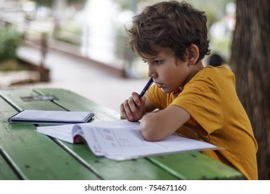 Side view of a schoolboy who thought about doing homework while sitting at a desk in the park