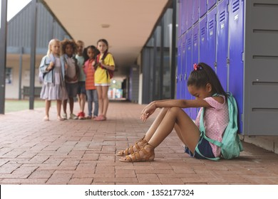 Side view of a schoolgirl sitting alone in school corridor while others school kids looking at her in background