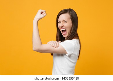 Side view of screaming young woman in white casual clothes looking camera, showing biceps, muscles isolated on bright yellow orange background in studio. People lifestyle concept. Mock up copy space