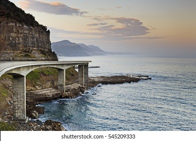 Side view of Sea Cliff Bridge on Grand Pacific Drive in Australia. Bright sunset over pacific ocean from scenic tourism motor way facing hilly coast.