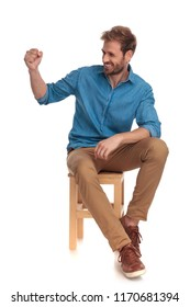 side view of a seated casual man laughing with fist up in the air on white background