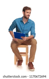 side view of a seated student with clipboard looking away on white background