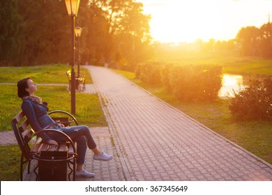 Side view seated woman on the bench enjoying nature in sunny day outdoors, charming young girl relaxing in the summer park, female student relaxing at campus, flare sun light