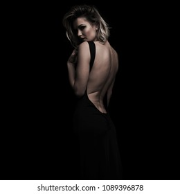 side view of seductive woman wearing an open back dress while standing on a black background
