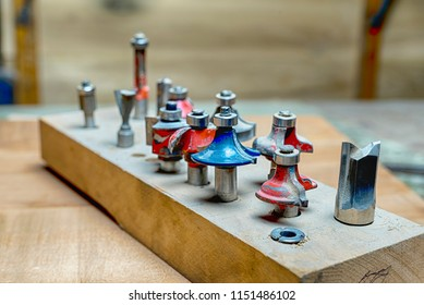 side view of a selection of red and blue woodworking router bits for router machine on a wooden surface