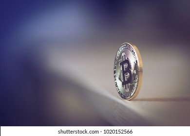 side view with selective focus of one bitcoin standing in equilibrium on edge of a wooden table