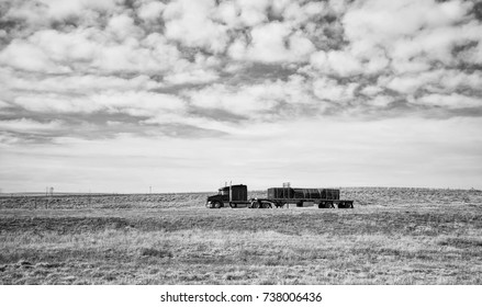 Side view of a semi truck hauling freight on a flatbed driving down interstate in a black and white Wyoming countryside landscape