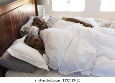 Side view of a senior African American couple sleeping in bedroom at home