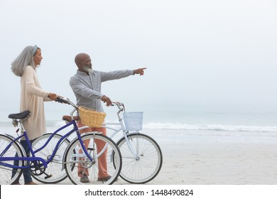 Side view of senior African-American couple walking with bicycles on beach. Authentic Senior Retired Life Concept