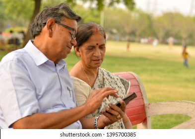 Side view of senior couple sitting in park on a red bench and looking at their smart phone and laughing in New Delhi, India