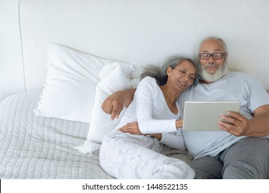 Side view of senior diverse couple lying in bed and watching digital tablet in bedroom. Authentic Senior Retired Life Concept