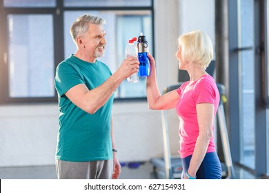Side view of senior fitness couple holding bottles with water gym