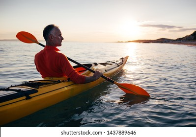 Side view of senior man paddling kayak on the sunset sea