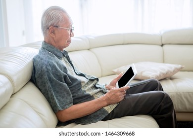 Side view of senior man using a digital tablet computer while sitting on the sofa. Shot at home