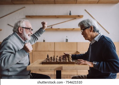 side view of senior multiethnic men playing chess