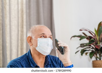 Side view of a senior optimistic man talking on the latest smartphone telephone wearing protective gloves and surgical mask during COVID-19 coronavirus pandemic diseases