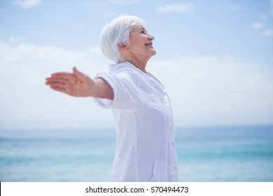 Side view of senior woman smiling while exercising at beach against sky