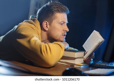 Side view serene unshaven man reading interesting volume while sitting at desk. Education concept