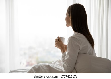 Side view serene woman woke up sitting on bed holds cup with morning coffee or tea enjoy new day, looking out the window admires view of city awakened in modern luxury apartment daydreaming concept